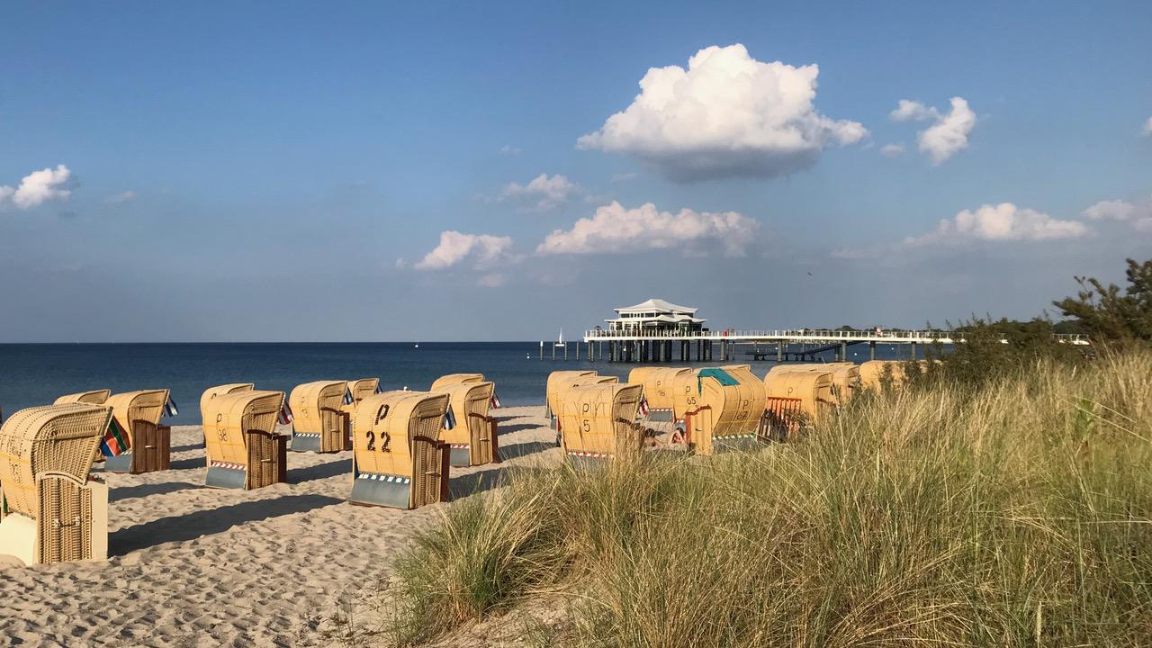 Blick von der Promenade in Timmendorfer Strand hinaus aufs Meer. Im Vordergrund stehen Strandkörbe. Im Hintergrund ist der Pavillon auf der Seebrücke zu sehen