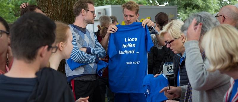 Eine Lions-Gruppe bereitet sich für den Spendenlauf vor. Auf den blauen T-Shirts steht mehrdeutig: Lions helfen laufend … seit 1917.