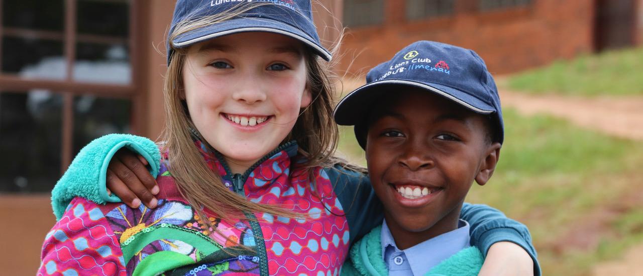 Zweit Kinder stehen eng nebeneinander, haben sich die Arme gegenseitig über die Schulter gelegt und lächeln in die Kamera.