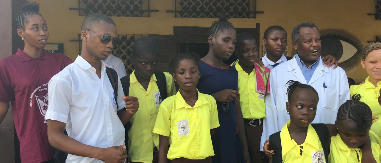 Sehbeeinträchtigte und blinde Kinder und Jugendliche stehen mit dem behandelnden Arzt vor der Augenklinik in Freetown Sierra Leone