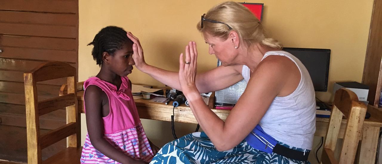 Mit einfachen Mitteln wird bei einem jungen Mädchen ein Sehtest durchgeführt