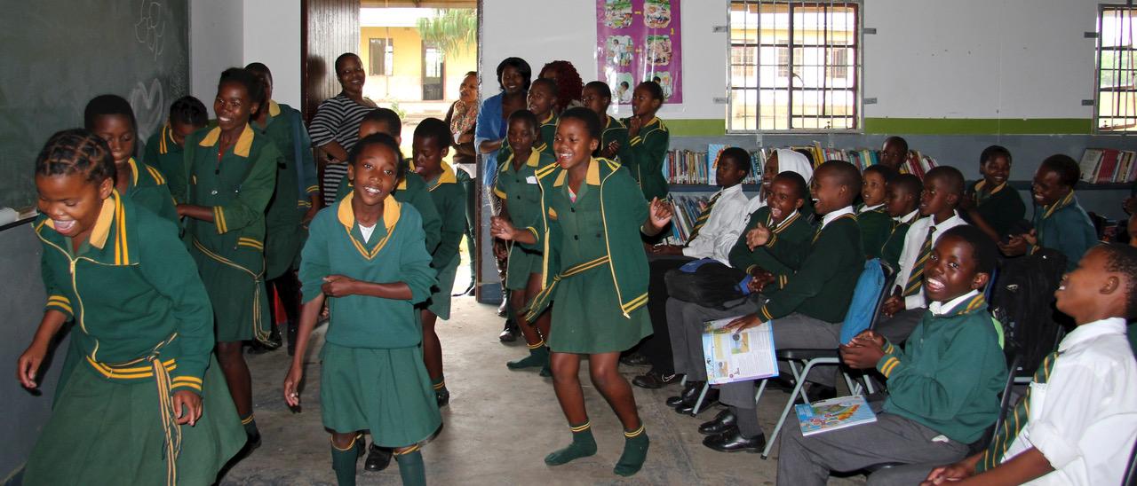 Die Schülerinnen führen strahlend einen Tanz in der Klasse auf