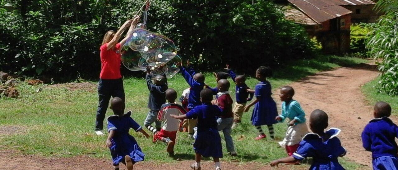 Kindergartenkinder laufen zur Betreuerin, die riesige Seifenblasen entstehen lässt