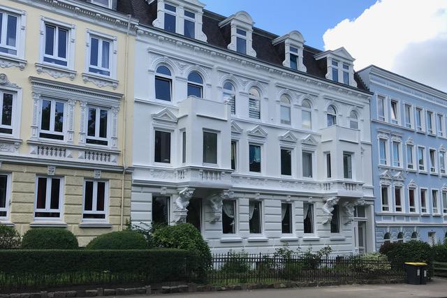Straßenzug mit Mehrfamilienhäusern mit verschiedenfarbigen Jugendstil-Fassaden in hellgelb, weiß und hellblau
