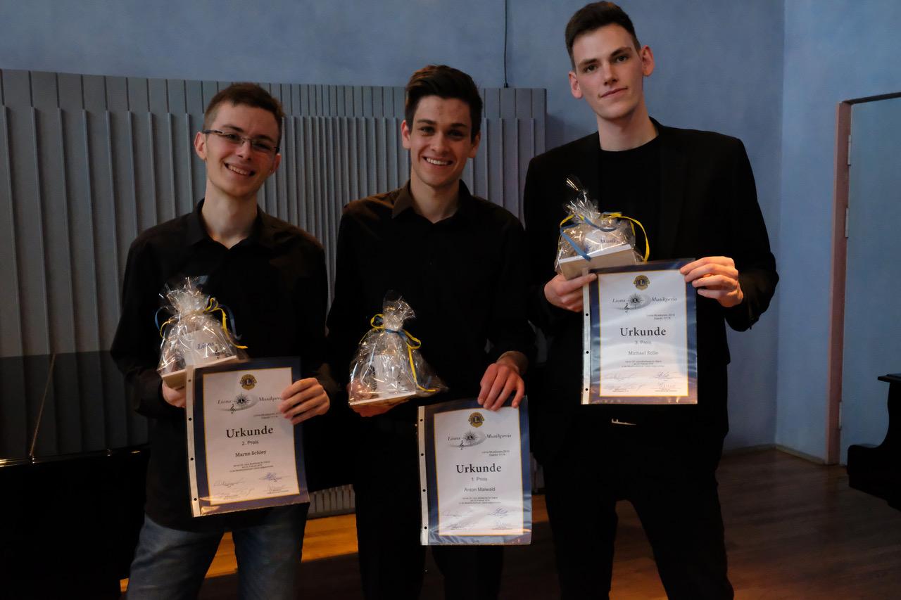 Drei junge Männer halten ihre Urkunden hoch.