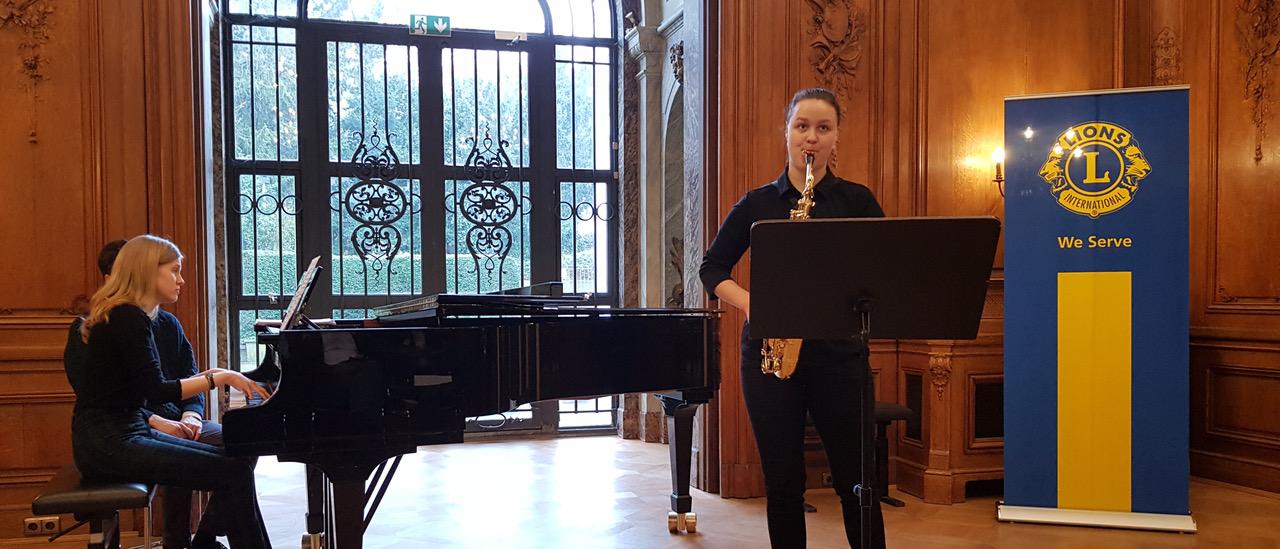 Eine junge Frau spielt beim Wettbewerb für Saxophone vor. Sie wird durch jemanden am Flügel begleitet.