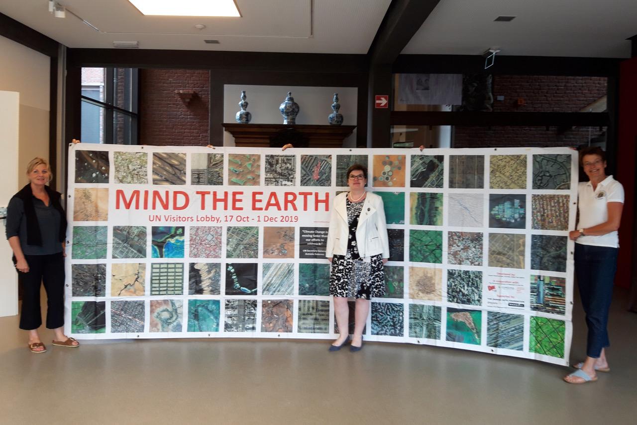 Dr. Heike Düselder, Claudia Kühne und Annette Brand stehen vor bzw. neben dem Banner, das die Fotoausstellung Mind the Earth in New York angekündigt hatte.