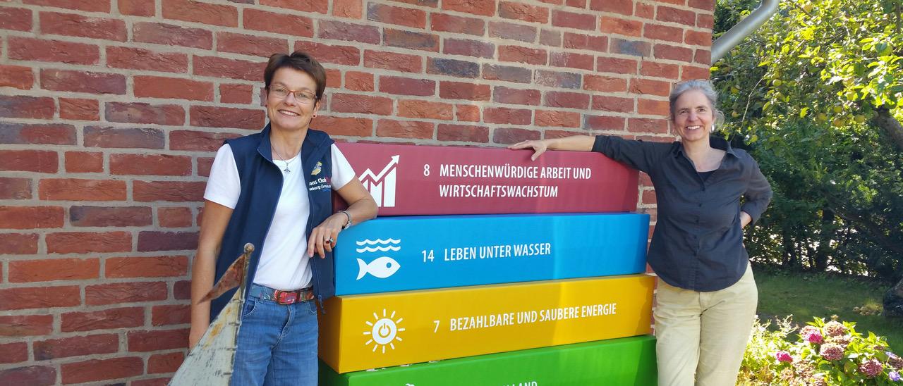 DG Annette Brand präsentiert zusammen mit einer Lionsfreundin ihres Clubs vier große 17-Ziel-Bauklötze